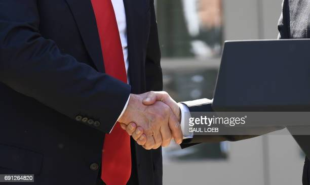 The head of the Environmental Protection Agency Scott Pruitt shakes hands with US President Donald Trump after he announced his decision to withdraw...