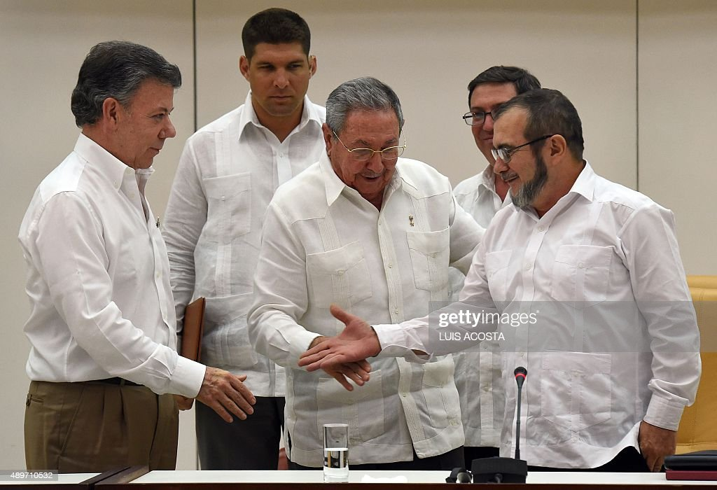 The head of the FARC guerrilla Timoleon Jimenez, aka Timochenko (R), extends his hand to shake with Colombian President Juan Manuel Santos (L) in front of Cuban President Raul Castro (C) during a meeting in Havana on September 23, 2015. The Colombian government and FARC rebels announced a key breakthrough in their nearly three-year peace talks Wednesday with the signing of a deal on justice for crimes committed during the five-decade conflict. The deal includes the creation of special courts and a broad amnesty, though this will not cover 'crimes against humanity, serious war crimes' and other offenses including kidnappings, extrajudicial executions and sexual abuse, said officials from Cuba and Norway, the guarantors in the talks. AFP PHOTO / Luis Acosta