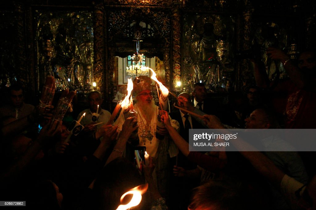 The head of the Greek Orthodox church in Bethlehem, Bishop Theofilactos, holds the 'Holy Fire' brought from the Church of the Holy Sepulchre in Jerusalem during the 'Holy Fire' ceremony in the West Bank town of Bethlehem on April 30, 2016. The ceremony is marked by the appearance of 'sacred fire' in the two cavities on either side of the Holy Sepulchre, in the Church of the Sepulchre in Jerusalem, and Christians all over the world light candles representing this 'Holy Fire'. The Holy Sepulchre in Jerusalem is the site of the tomb of Jesus Christ according to Christian tradition. / AFP / MUSA