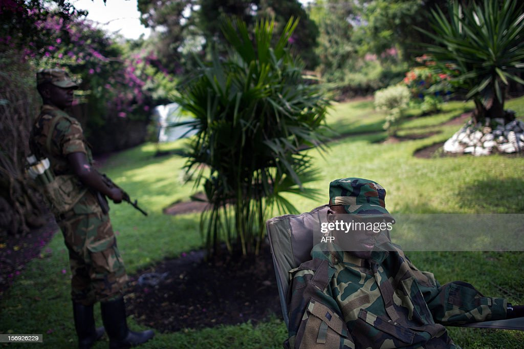 The head of the M23 rebel military forces, Brigadier-General Sultani Makenga (R), sits on November 25, 2012 in the yard of a military residence in Goma in the east of the Democratic Republic of the Congo. Over half a million people have been displaced in eastern Congo since the outbreak of the M23 rebellion. Diplomatic efforts continued on November 25 to resolve the crisis in eastern DR Congo, with an M23 rebel leader expected to hold further talks with President Joseph Kabila as the African Union called on the rebels to pull out from Goma.