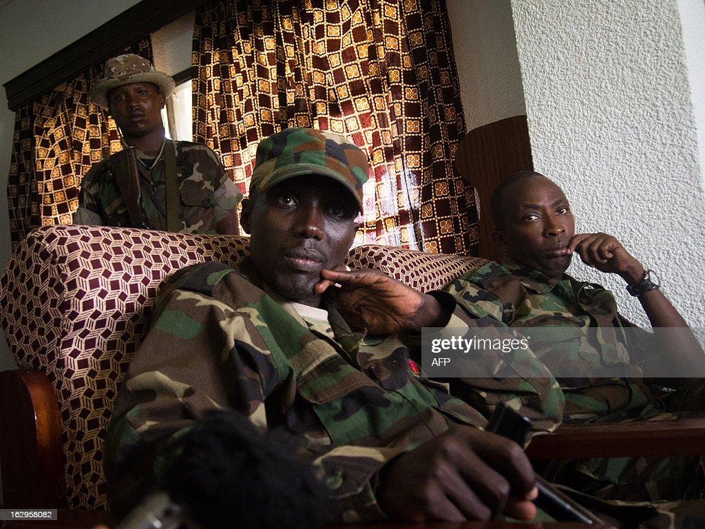 The head of the M23 rebel military forces, Brigadier-General Sultani Makenga (front L) from the Democratic Republic of the Congo, sits in a room on March 2, 2013 surrounded by his guards in Bunagana. Makenga is about to receive members of JVM (Joint Verification Mechanism) which was founded by ICGLR, the 11-country International Conference on the Great Lakes Region. The Presidents of Africa's Great Lakes regional nations will meet on March 3, for the latest bid to ink a deal on an accord aimed at pacifying the war-torn east of the Democratic Republic of the Congo.