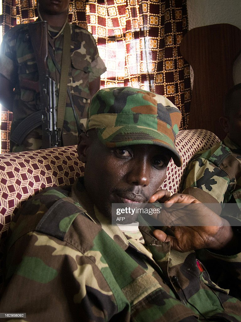 The head of the M23 rebel military forces, Brigadier-General Sultani Makenga (front L) from the Democratic Republic of the Congo, sits in a room on March 2, 2013 in Bunagana. Makenga is about to receive members of JVM (Joint Verification Mechanism) which was founded by ICGLR, the 11-country International Conference on the Great Lakes Region. The Presidents of Africa's Great Lakes regional nations will meet on March 3, for the latest bid to ink a deal on an accord aimed at pacifying the war-torn east of the Democratic Republic of the Congo. AFP PHOTO/MICHELE SIBILONI