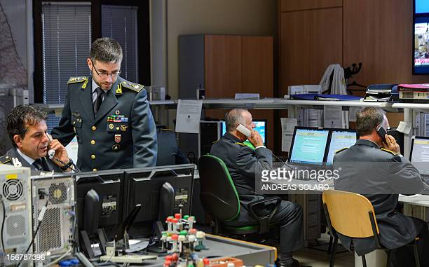 The head of the operations Italian lieutenant colonel Davide Cardia of the Guardia di Finanzia stands next officers in the operation room of the...