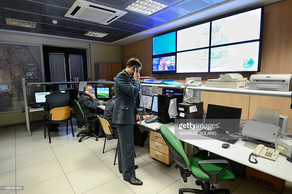 The head of the operations, Italian lieutenant colonel Davide Cardia of the Guardia di Finanzia, speaks on the telephone in the operation room of the regional comando of the Lazio area on November 20, 2012 in Rome. The operation room of the Guardia di Finanza receives phone calls and launches operations related to tax abuses and tax controls. AFP PHOTO / ANDREAS SOLARO