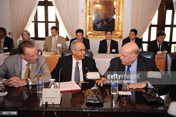 The head of the Organization of American States Jose Miguel Insulza speaks with Canadian Minister of Foreign Affairs Peter Kent and a representative...