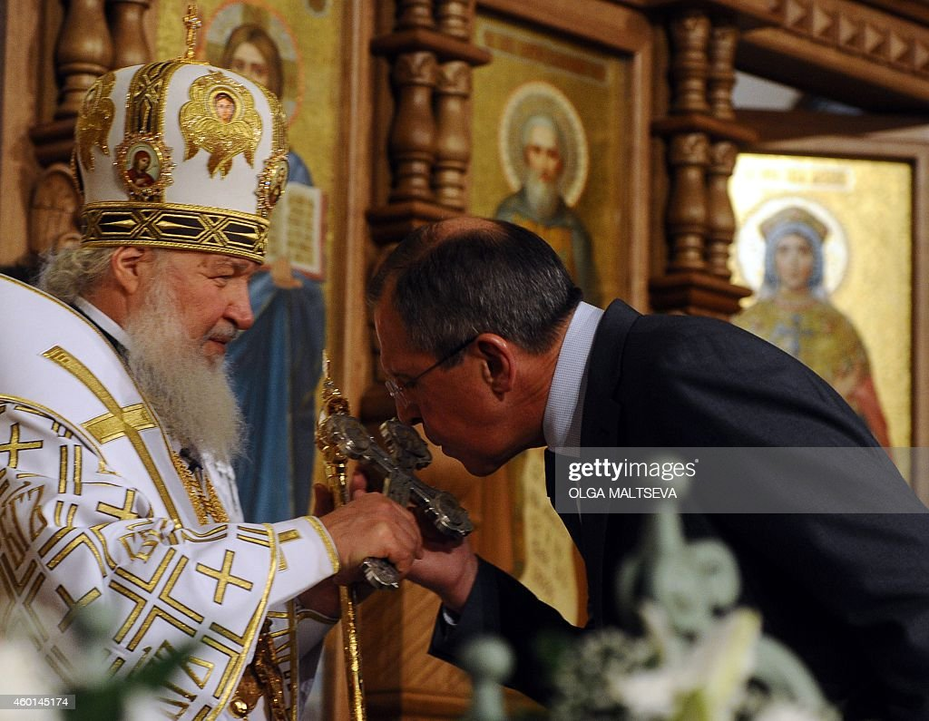 The head of the Russian Orthodox Church Patriarch Kirill holds the cross as Russian Foreign Minister Sergei Lavrov kisses it during the service at...