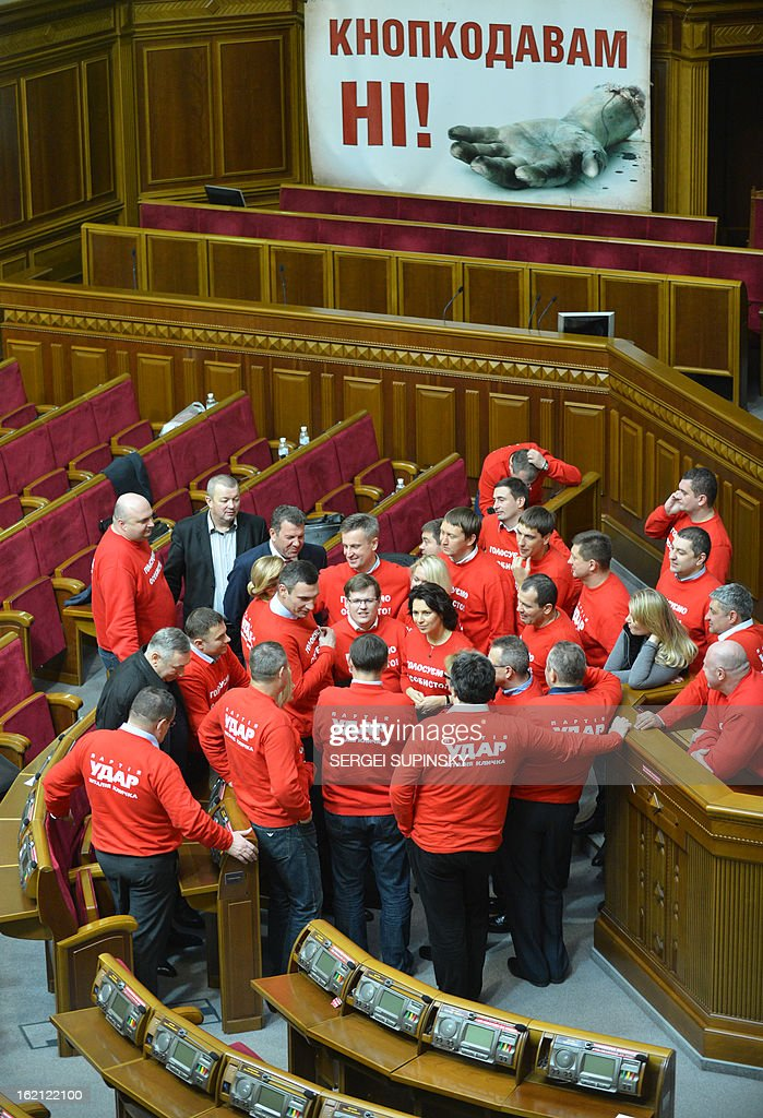 "The head of the Ukrainian opposition party UDAR ( Punch) and boxing heavyweight World champion Vitaliy Klitschko (C) speaks on February 19, 2013 to UDAR deputies wearing T-shirts signed 'Vote personally"" as they block the parliamentary tribune after hanging a placard showing a severed hand and reading 'No button pushers!"" to prevent the opening of the parliamentary session in Kiev. The opposition has been blocking the parliament sittings since February 4, demanding that pro-government deputies end the practice of voting for their absent colleagues in violation of the constitution."