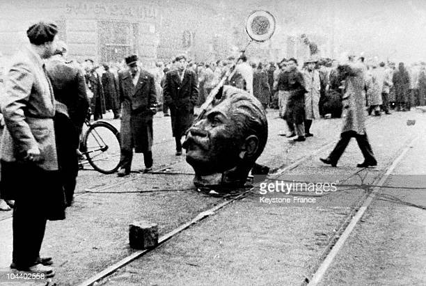 The head of this statue of STALIN was twisted off by Hungarian protesters Part of the statue of STALIN is lying in the middle of the street