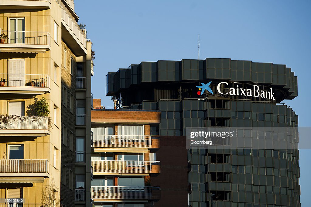 The headquarters of CaixaBank SA stand beyond residential apartments in Barcelona, Spain, on Tuesday, Jan. 8, 2013. Banco Santander SA, Spain's biggest lender, will offer 263 million euros ($345 million) in stock to buy out minority investors in its Banco Espanol de Credito SA retail unit and close 700 local branches to cut costs. Photographer: David Ramos/Bloomberg via Getty Images