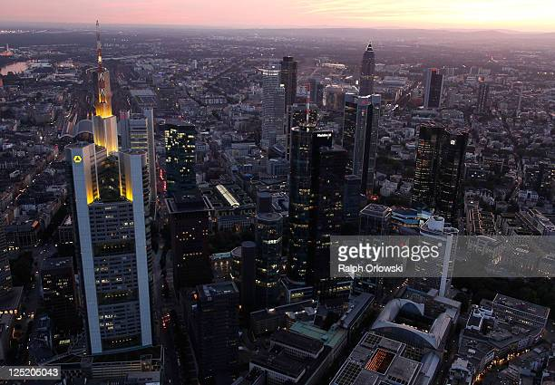 The headquarters of Commerzbank and the twin towers of Deutsche Bank stand illuminated amid the skyline in this aerial picture of the financial...