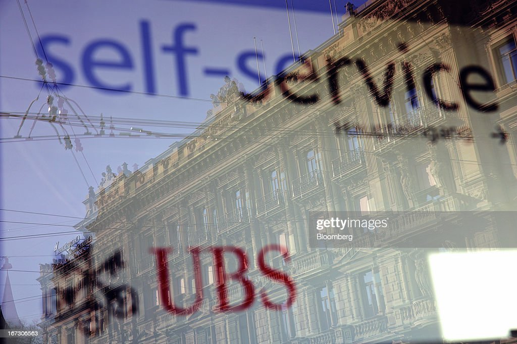 The headquarters of Credit Suisse Group AG are reflected in the window of a UBS AG bank branch in Zurich, Switzerland, on Wednesday, April 24, 2013. Credit Suisse Group AG, the second- biggest Swiss bank, posted a jump in first-quarter profit as year-earlier charges related to its own debt and bonus payments weren't repeated. Photographer: Gianluca Colla/Bloomberg via Getty Images