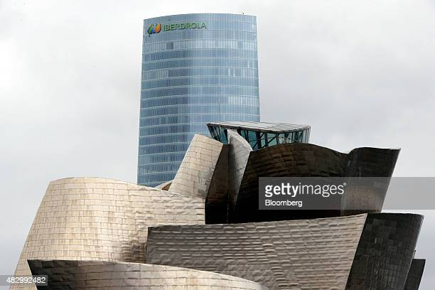 The headquarters of Iberdrola SA stands beyond the Guggenheim Museum in Bilbao Spain on Tuesday Aug 4 2015 Iberdrola SA Spain's largest utility...