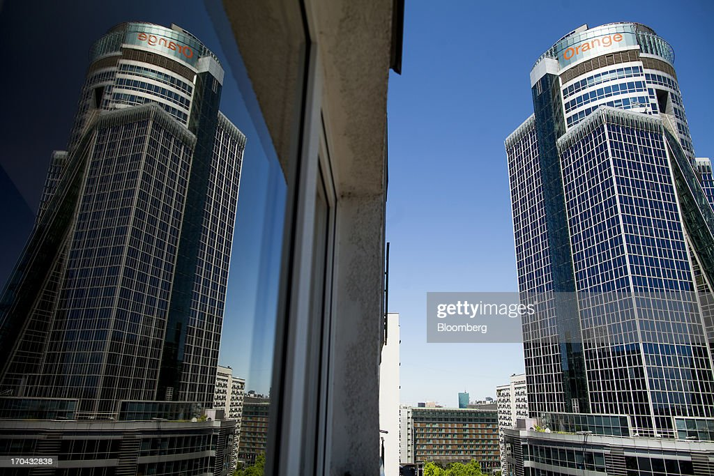 The headquarters of Orange Polska, right, also known as Telekomunikacja Polska SA (TPSA), Poland's national telecommunications company, is reflected in a neighboring office building in Warsaw, Poland, on Wednesday, June 12, 2013. Cable providers are being drawn to Poland, the European Union's biggest eastern economy, because penetration levels are half that of neighboring Germany even as unemployment rises, according to a website presentation by the country's biggest TV network, Cyfrowy Polsat SA. Photographer: Bartek Sadowski/Bloomberg via Getty Images