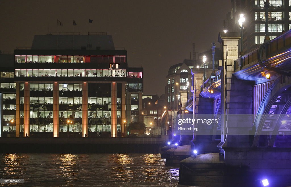 The headquarters of the Financial Times newspaper, left, are bathed in pink light to mimic the color of the publication's paper, as part of their 125th anniversary celebrations, in London, U.K. on Wednesday, Feb. 13, 2013. Pearson Plc, owner of the Financial Times newspaper, cut its forecast for 2012 and predicted a difficult 2013, as tougher market conditions hit earnings at its professional education and FT Group units. Photographer: Chris Ratcliffe/Bloomberg via Getty Images