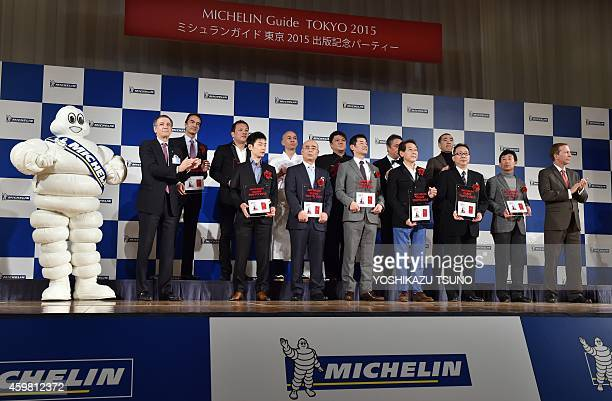The heads of threestar restaurants selected by the new Michelin Guide Tokyo 2015 guidebook pose at a photo session during the publication...
