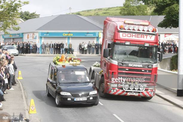 The hearse carrying the coffin of Paul Doherty passes a truck carrying wreaths before his funeral at St Mary's Church in Clonmany Co Donegal Mr...
