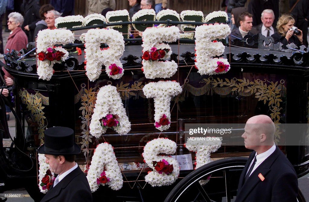 The hearse carrying the coffin of Reggie Kray drives along the route towards St. Matthew's Church in Bethnal Green in East London 11 October 2000. Kray, who died of cancer 10 days ago, shortly after being released from prison after serving more than 30 years, was one of Britain's most feared gangsters. The Kray twins, Ronnie and Reggie, and older brother Charlie held a mafia-like grip on London's East End during the 1960's. Reggie and Ronnie were convicted of murder and sentenced to life in 1969.