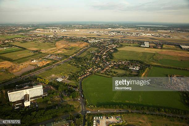 The Heathrow Holiday Inn Hotel bottom left and residential housing and farmland in the village of Sipson center sit in the foreground as aircraft and...