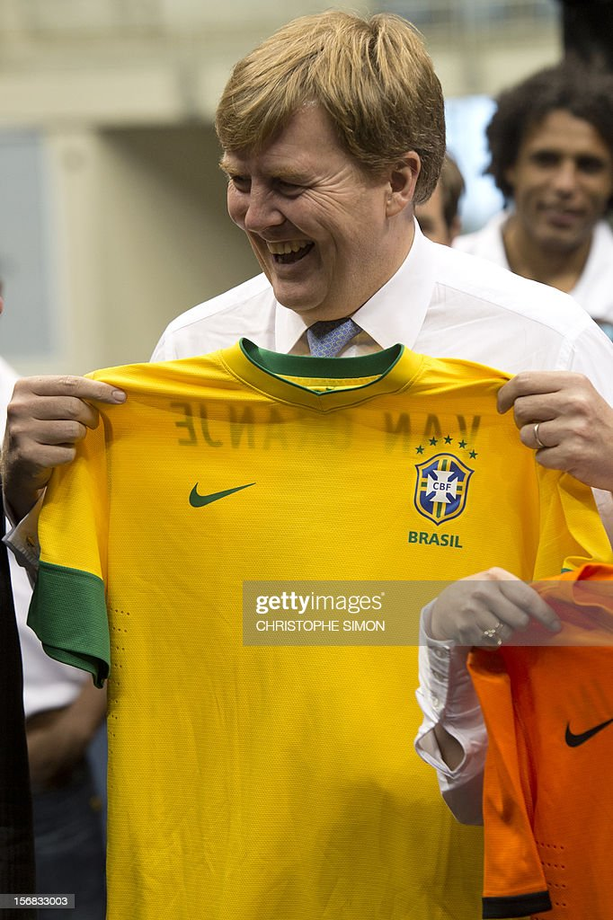 The heir to the Dutch throne Willem-Alexander holds a jersey of the Brazilian national football team given to him as a gift during the presentation of Panna Knock-Out, a form of football originated in Holland, in Rio de Janeiro on November 22, 2012. The Dutch royals are on a five-day visit to Brazil. AFP PHOTO/Christophe Simon