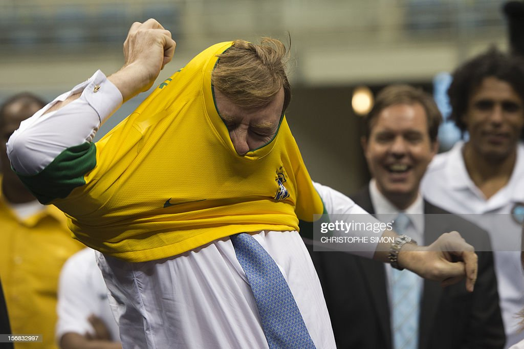 The heir to the Dutch throne Willem-Alexander puts a jersey of the Brazilian national football team given to him as a gift during the presentation of Panna Knock-Out, a form of football originated in Holland, in Rio de Janeiro on November 22, 2012. The Dutch royals are on a five-day visit to Brazil. AFP PHOTO/Christophe Simon