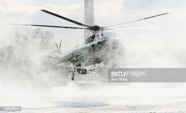 The helicopter that will serve as Marine One blows up snowflakes from the South Lawn as it lands at the White House prior to the departure of...