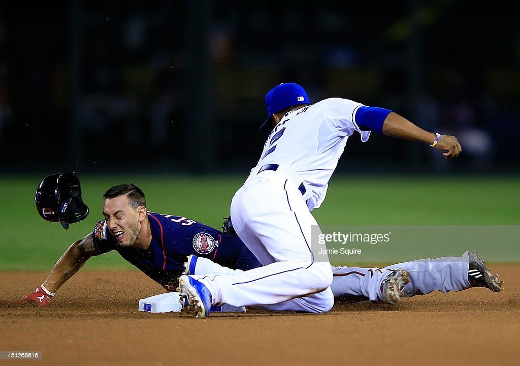 The helmet of Jordan Schafer #1 of the Minnesota Twins pops off as he slides safely into second base for a steal as Alcides Escobar #2 of the Kansas City Royals is late applying the tag during the 5th inning of the game at Kauffman Stadium on August 27, 2014 in Kansas City, Missouri.