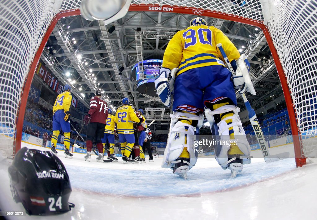 The helmet of Mikelis Redlihs of Latvia sits in the net after shoving in front of Henrik Lundqvist of Sweden in the second period during the Men's...