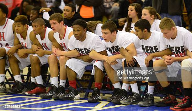 The Herndon bench looks on as Dorian Johnson shoots free throws at the end of regulation during the Virginia 6A North region semifinals against WT...