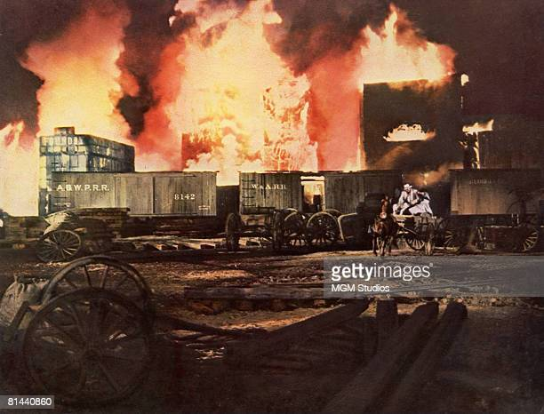 The hero and heroine drive through the burning city of Atlanta in a dramatic scene from the MGM film 'Gone with the Wind'