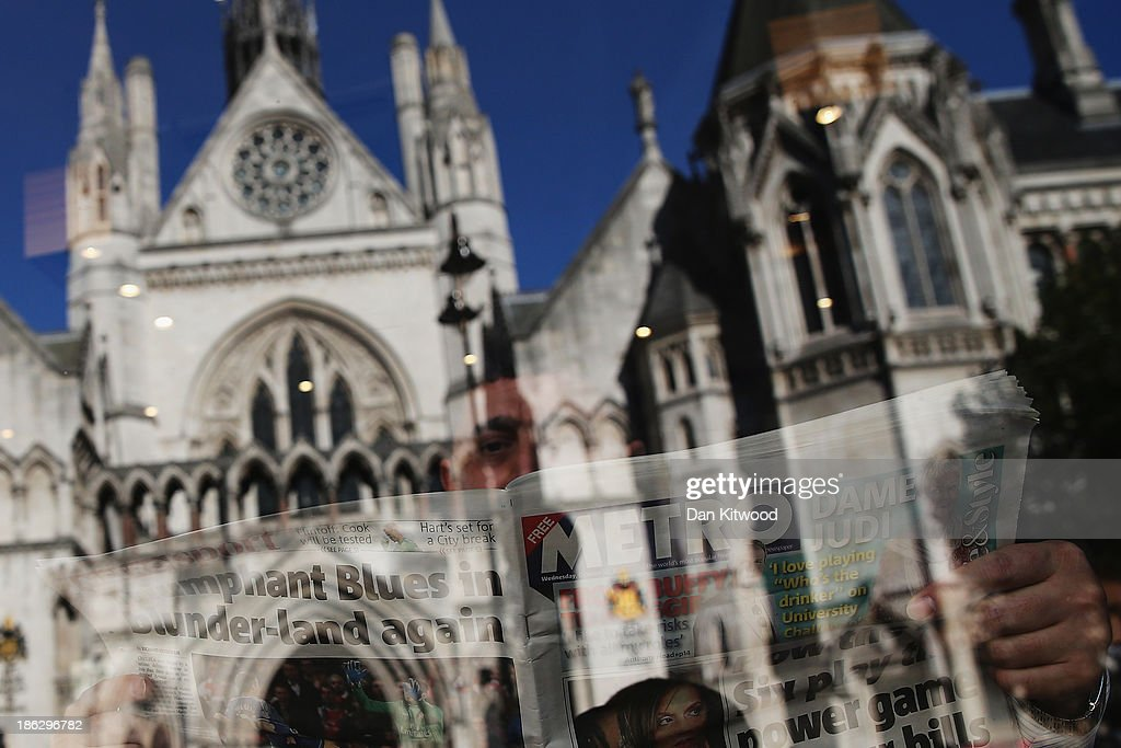 The High Court at the Royal Courts of Justice is reflected in a cafe window as a customer reads a newspaper on October 30 2013 in London England The...