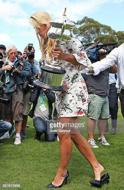 The high heeled shoe of Angelique Kerber of Germany becomes stuck in the lawn as she holds the Daphne Akhurst Memorial Cup during a photocall at...