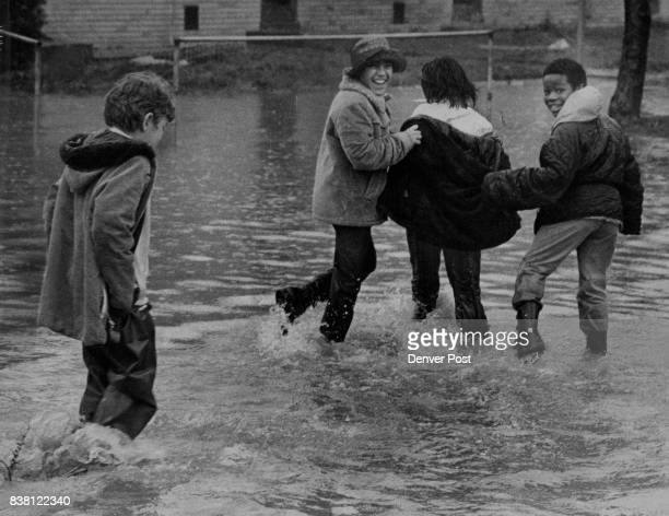 The high water from rain washing into low spots was a lark for these boys who live in Stapleton Homes a Denver Housing Authority complex at51st Ave...