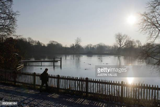 The Highgate Men's Bathing Pond is pictured in north London on December 12 at sunrise on a freezing winter morning / AFP PHOTO / Justin TALLIS