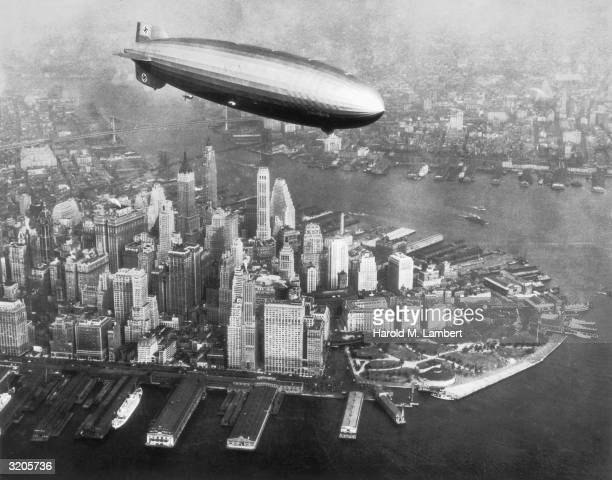 The Hindenburg airship flies over the Hudson River and downtown Manhattan New York City
