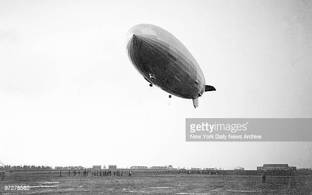 The Hindenburg dirigible lazily floats down toward the mooring mast moments before explosion