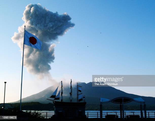 The Hiomaru Japanese national flag flutters atop a flagpole built at a roadside station against the backdrop of Mount Sakurajima a volcano on...