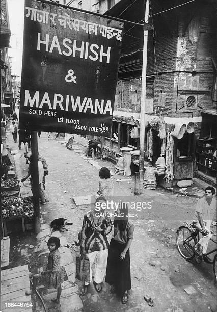 Religion And Hashish Deux hippies espagnols dans une rue de KATMANDOU devant une boutique où l'on trouve hachisch et marijuana en vente libre