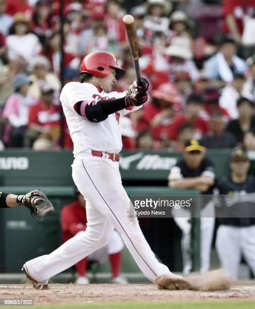 The Hiroshima Carp's Yoshihiro Maru hits a home run during the eighth inning of his team's 32 interleague win over the SoftBank Hawks on June 17 at...