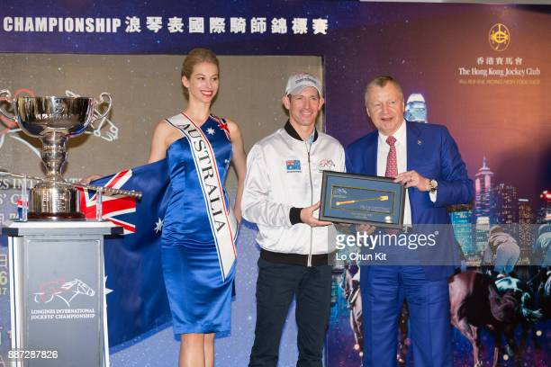 The HKJC's Chief Executive Officer Mr Winfried EngelbrechtBresges presents goldplated mini whips to participating jockey Hugh Bowman during the...
