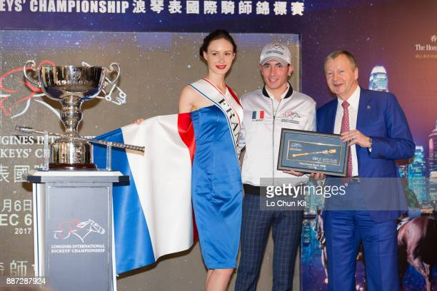 The HKJC's Chief Executive Officer Mr Winfried EngelbrechtBresges presents goldplated mini whips to participating jockey PierreCharles Boudot during...