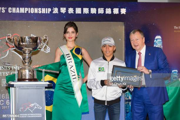 The HKJC's Chief Executive Officer Mr Winfried EngelbrechtBresges presents goldplated mini whips to participating jockey Leandro Henrique during the...