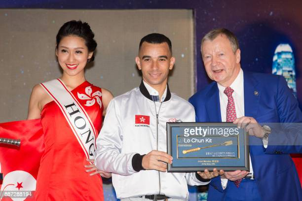 The HKJC's Chief Executive Officer Mr Winfried EngelbrechtBresges presents goldplated mini whips to participating jockey Joao Moreira during the...
