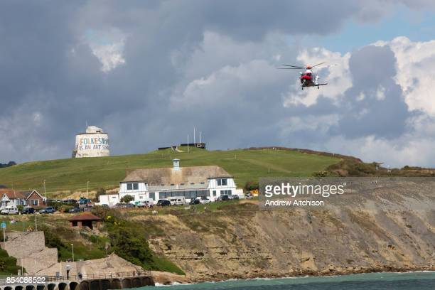 The HM Coastguard rescue helicopter flying over the Folkestone is an Art School banner attached to Folkestones most prominent Martello Tower on the...