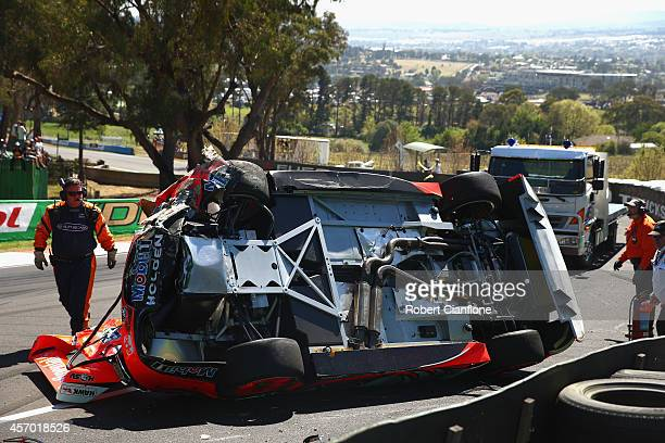 The Holden Racing Team Holden of Warren Luff is seen on its side after a crash with Craig Lowndes driver of the Red Bull Racing Australia Holden...