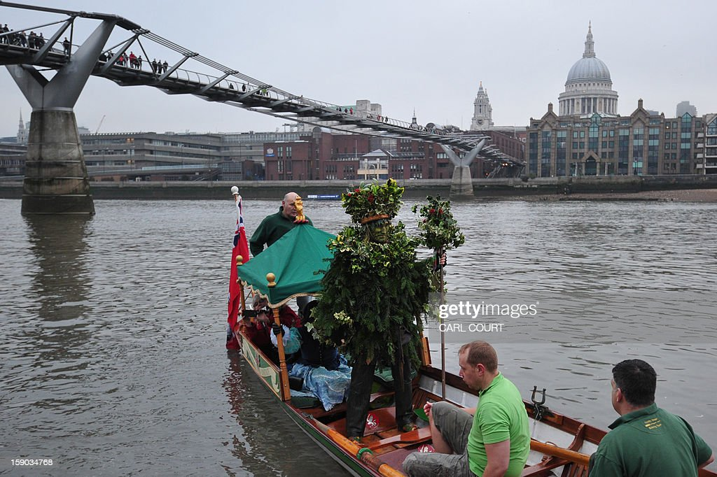 The Holly Man, the winter guise of the Green Man, a character from pagan myths and folklore, arrives by boat to act in a free performance with The Bankside Mummers group (from the Lions part) near the Globe Theatre in central London on January 6, 2013, in celebration of Twelfth Night, marking the end of the twelve days of winter festivities. Twelfth Night celebrations in the traditional agricultural calendar mark a last chance to make merry before returning to the rigours of work on Plough Monday. AFP PHOTO / CARL COURT