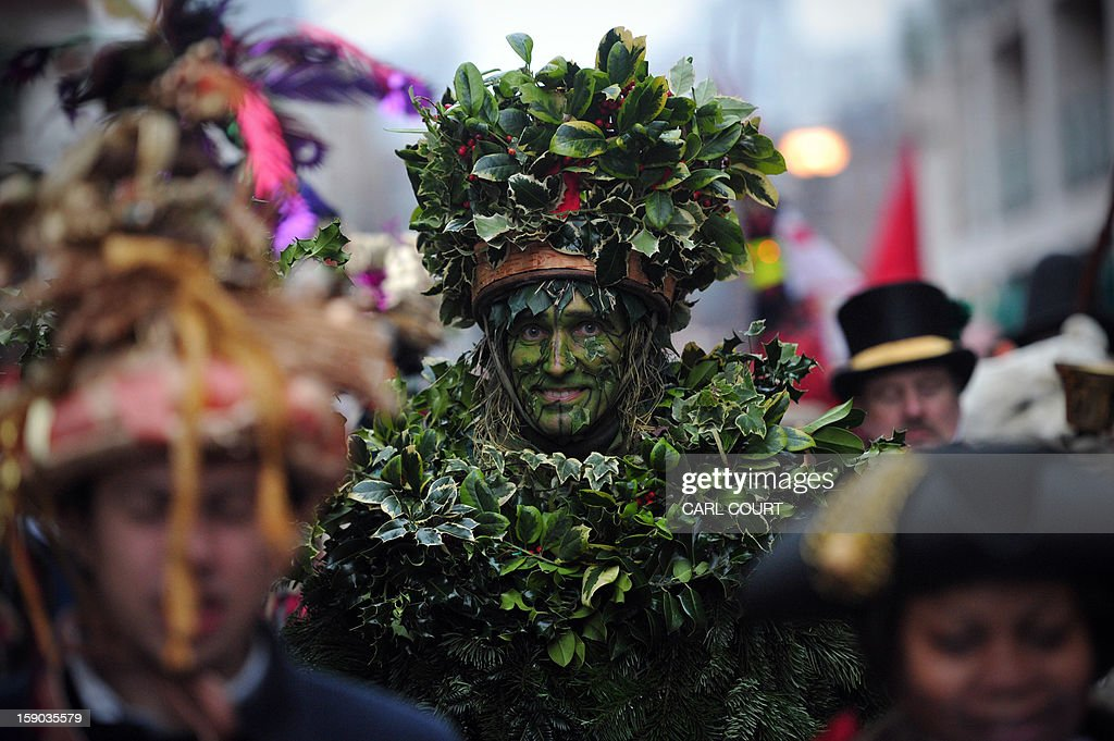 The Holly Man, the winter guise of the Green Man, a character from pagan myths and folklore, joins with other actors from the Bankside Mummers group (from the Lions part) and members of the public in a procession after a folk play in central London on January 6, 2013, in celebration of Twelfth Night, marking the end of the twelve days of winter festivities. Twelfth Night celebrations in the traditional agricultural calendar mark a last chance to make merry before returning to the rigours of work on Plough Monday. AFP PHOTO / CARL COURT