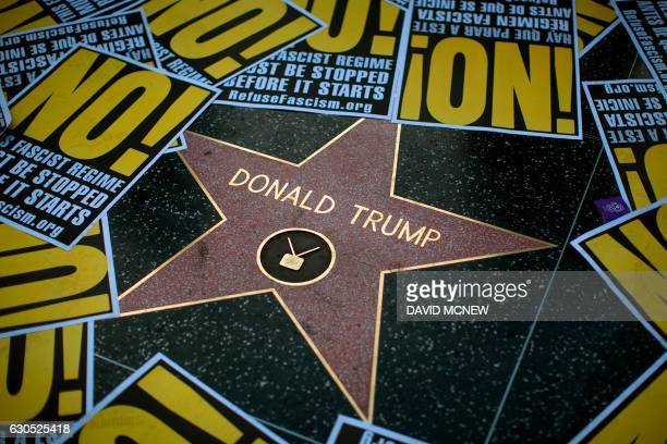 TOPSHOT The Hollywood Walk of Fame star for Donald Trump is framed in protest posters during a demonstration in reaction to a Twitter post by US...