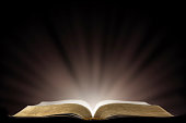 A Book that looks like a Bible Open in a Dark Room with Light Pouring Out of it representing enlightmentThe Holy Spirit on a Black Table with Light coming from the edge