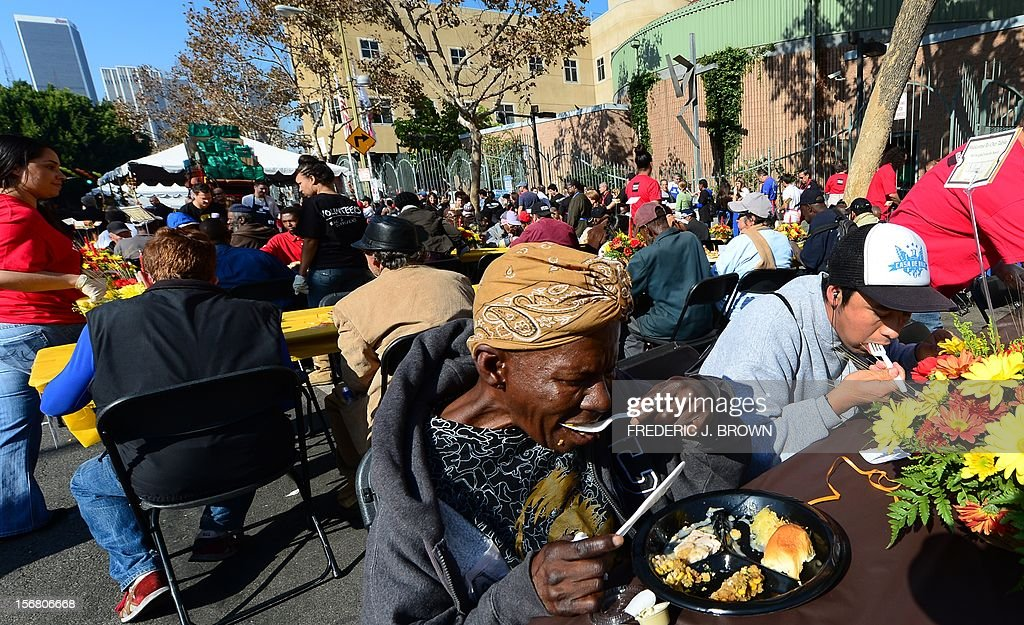 The homeless and less fortunate enjoy their lunch at the LA Mission's annual Thanksgiving meal in LA's skid row served by celebrities on November 21, 2012 in California. The LA Mission started as a soup kitchen for men of the depression era in 1936 and continues serving meals each day, providing emergency shelter, and helping men and women restore their lives to get back on their feet. AFP PHOTO / Frederic J. BROWN