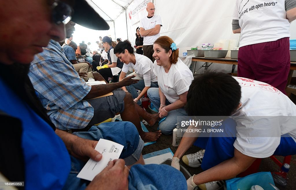 The homeless enjoy a foot wash at the Los Angeles Mission's Good Friday event on Skid Row on March 29, 2013 in Los Angeles, California. Celebrities and volunteers joined together in giving something back to this community of the homeless, among the largest in the US, who were fed a fully-prepared meal and had the opportunity to be given foot washing and hygiene kits. Foot washing, a symbolic ritual of humbleness and respect derived from Jesus Christ's washing of his disciples feet at the Last Supper, was offered by the Los Angeles Health Center and volunteers. AFP PHOTO/Frederic J. BROWN